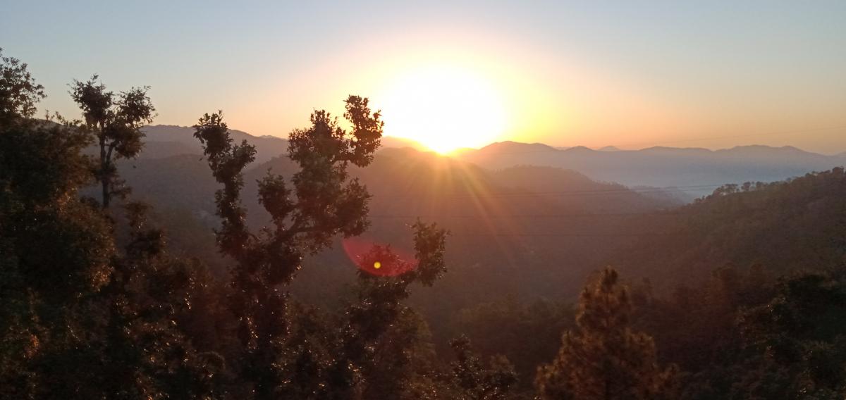 धनगढीः जंगलमा ढकमक्क लालीगुँरास। सबैतिर ठूला पहाड तथा उत्तरमा हिमालको दृश्य। पूर्वमा बिहानको उदाउँदो सूर्य।